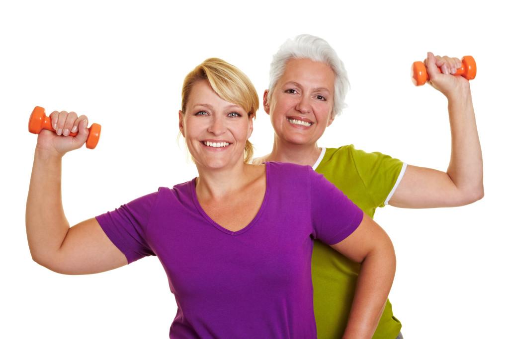Zwei lächelnde Frauen machen Rückentraining mit Hanteln